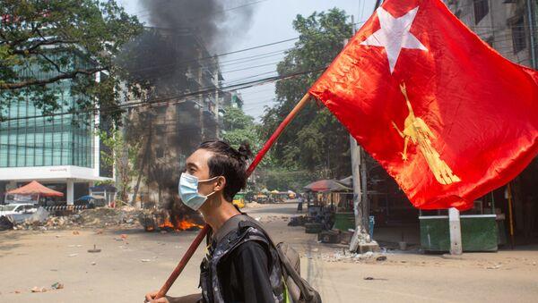 Một người đàn ông cầm cờ của Liên đoàn Quốc gia vì Dân chủ trong cuộc biểu tình phản đối đảo chính quân sự ở Yangon, Myanmar. - Sputnik Việt Nam