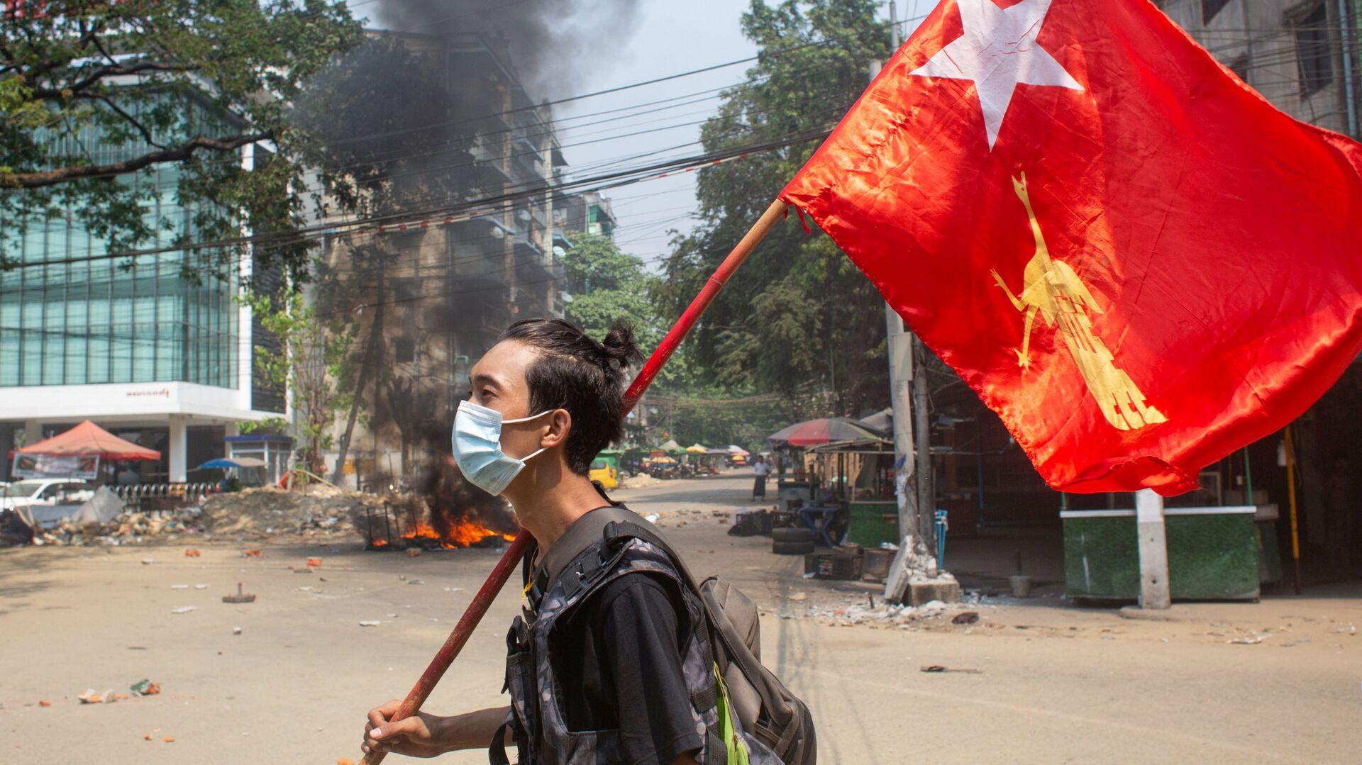 Một người đàn ông cầm cờ của Liên đoàn Quốc gia vì Dân chủ trong cuộc biểu tình phản đối đảo chính quân sự ở Yangon, Myanmar. - Sputnik Việt Nam, 1920, 02.04.2021
