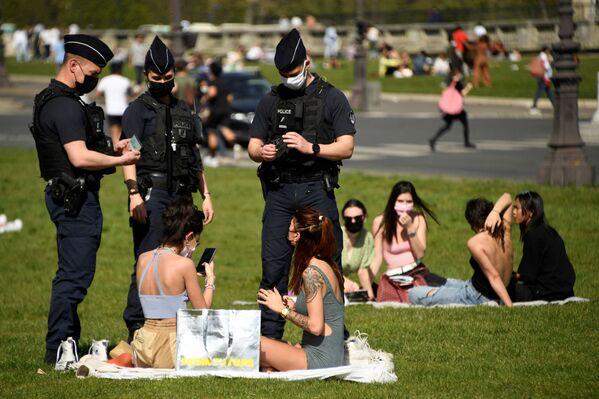 Nhân viên cảnh sát Pháp kiểm tra những người đang nghỉ ngơi trên bãi cỏ ở Paris, Pháp - Sputnik Việt Nam
