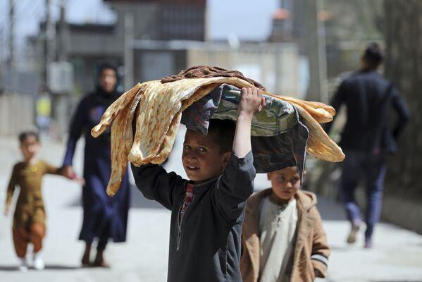 Cậu bé với bánh mì Lavash trên đầu ở một đường phố Kabul, Afghanistan - Sputnik Việt Nam