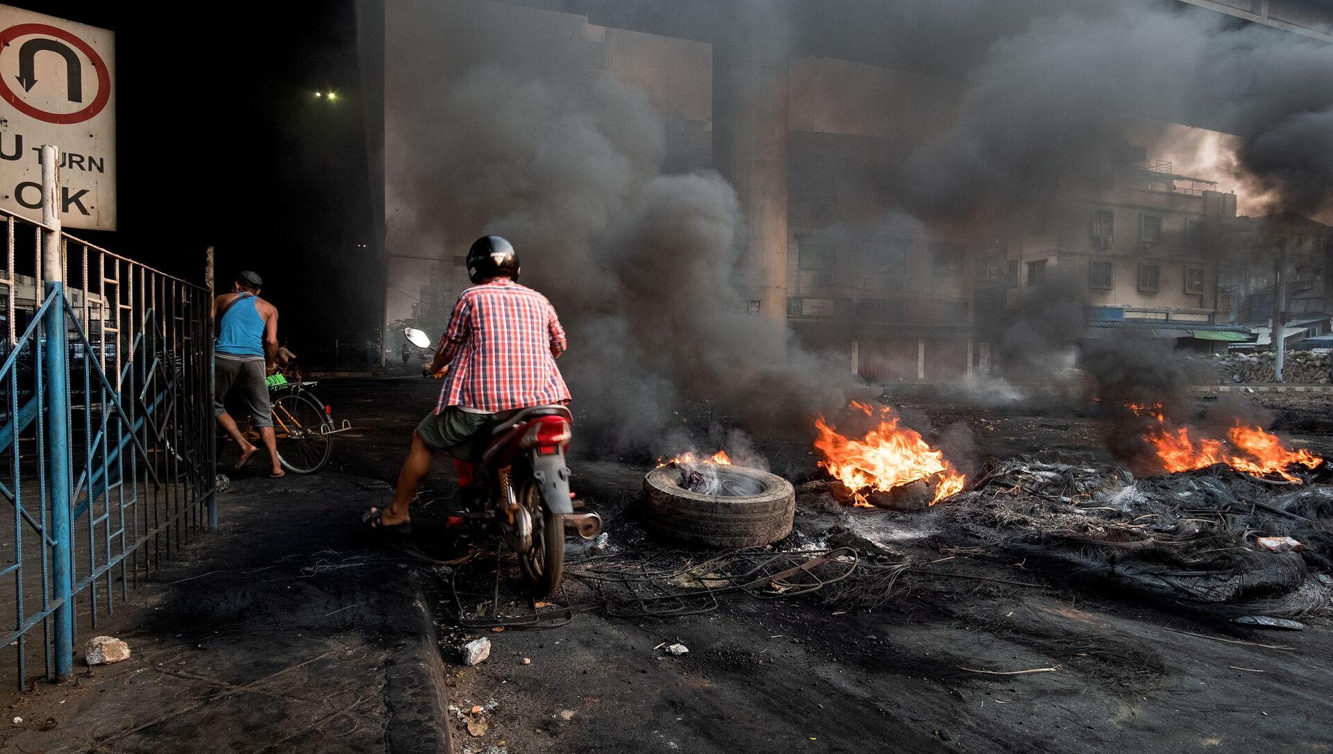Khói bốc lên từ lốp xe đang cháy bốc lên tạo ra khói bao phủ trong một cuộc trấn áp tại Bayint Naung Junction ở Yangon, Myanmar ngày 16 tháng 3 năm 2021, trong bức ảnh do Reuters thu được. - Sputnik Việt Nam, 1920, 04.05.2021