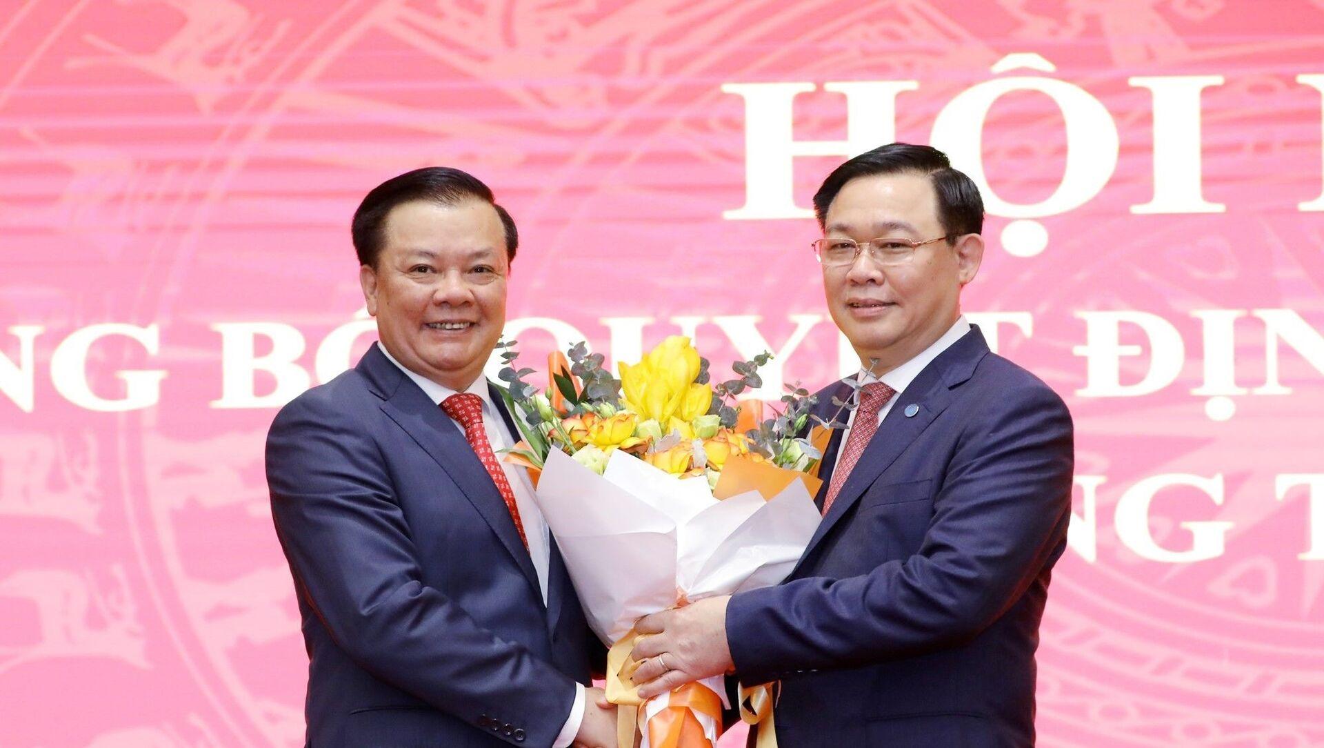 Chủ tịch Quốc hội Vương Đình Huệ tặng hoa chúc mừng tân Bí thư Thành ủy Hà Nội Đinh Tiến Dũng. - Sputnik Việt Nam, 1920, 03.04.2021