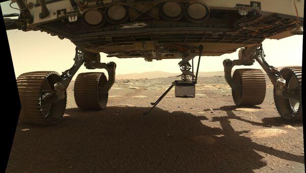 Máy bay trực thăng Ingenuity được gắn vào đáy của xe tự hành sao Hỏa Perseverance. - Sputnik Việt Nam