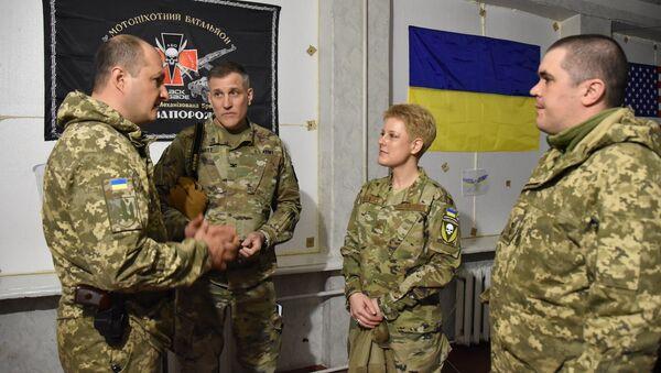 """Đại tá Brittany Stewart, trưởng phái đoàn Hoa Kỳ, Tùy viên Quân đội và Quốc phòng mặc áo có gắn sọc vải của lữ đoàn in hình đầu lâu và dòng chữ Ukraina hay là chết"""" - Sputnik Việt Nam"""