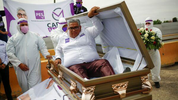 Chính trị gia Carlos Mayorga diễu khắp thành phố trên chiếc xe tang, còn bản thân ông ta nằm trong quan tài. - Sputnik Việt Nam
