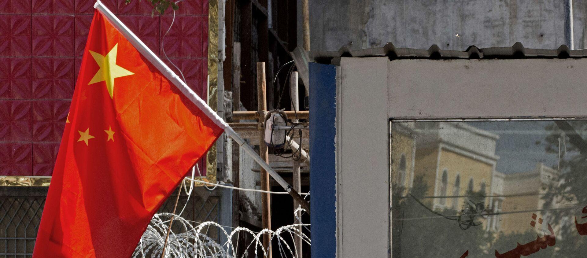 Người dân đứng gần hàng rào có dây thép gai và quốc kỳ Trung Quốc ở khu vực Tân Cương, miền tây Trung Quốc. - Sputnik Việt Nam, 1920, 16.04.2021