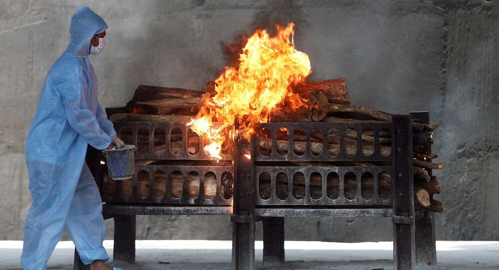 Công nhân mặc thiết bị bảo hộ cá nhân phun chất lỏng dễ cháy lên giàn hỏa táng xác người đàn ông chết vì COVID-19, Ấn Độ.
