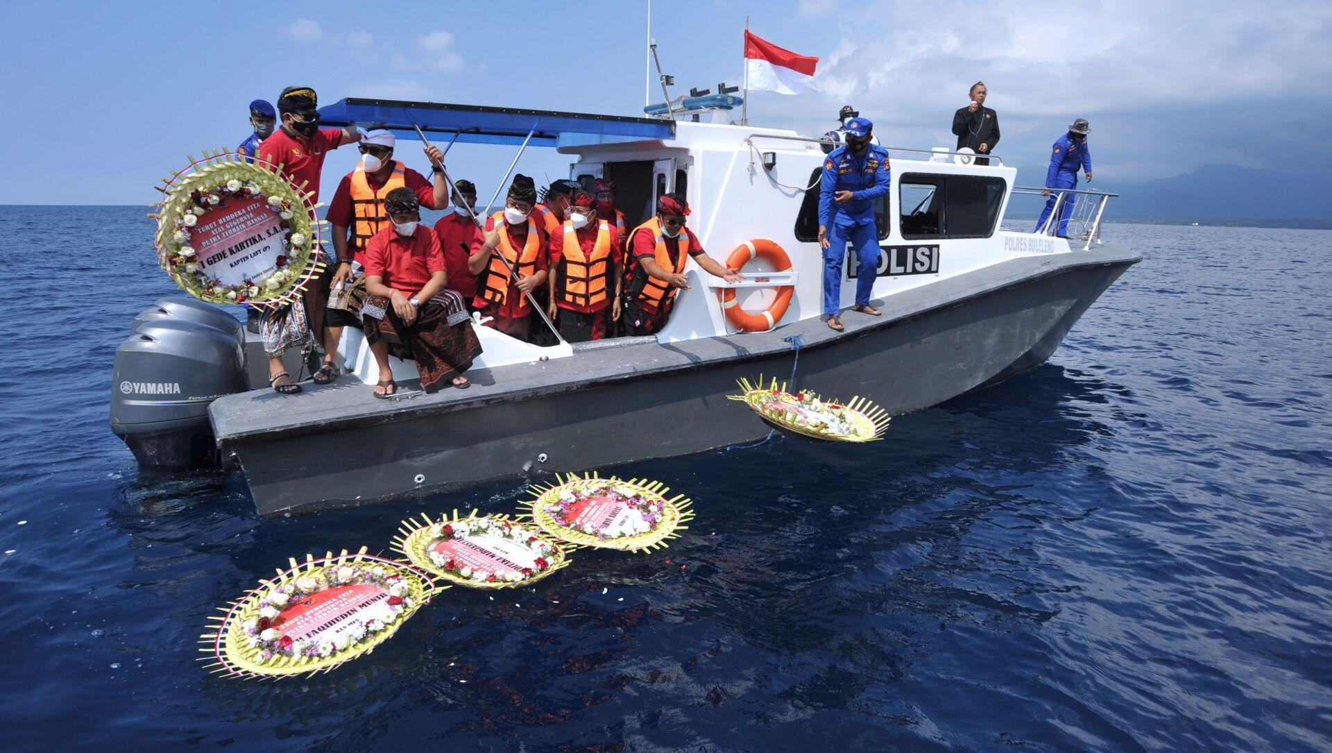Mọi người từ trên tàu ném hoa và cánh hoa có đề tên các thành viên thủy thủ đoàn tàu ngầm bị chìm KRI Nanggala-402, Indonesia. - Sputnik Việt Nam, 1920, 26.04.2021