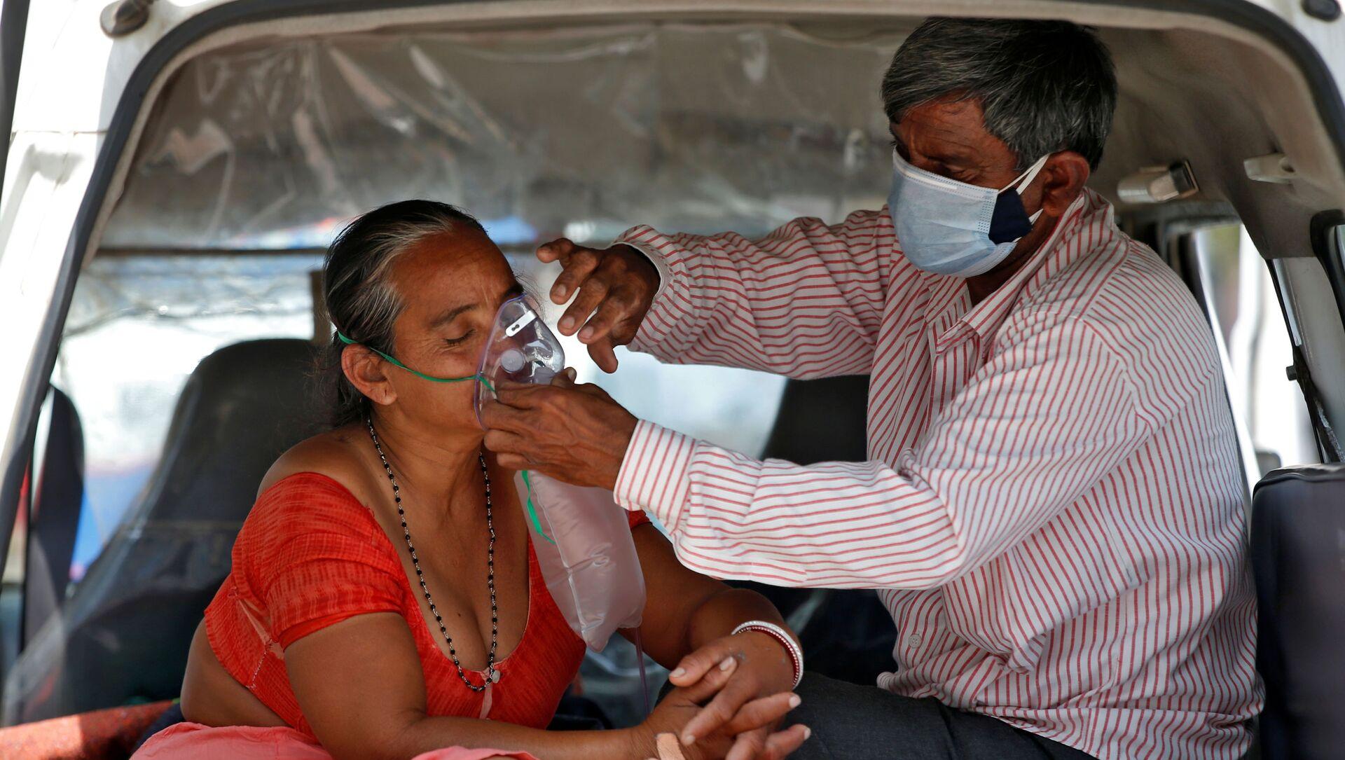 Người chồng điều chỉnh mặt nạ dưỡng khí cho vợ trong khi hai người đang ngồi trong xe chờ được nhập viện, Ấn Độ - Sputnik Việt Nam, 1920, 21.06.2021