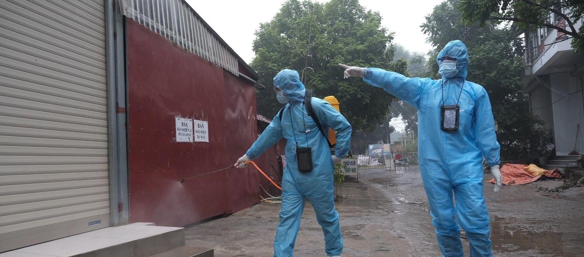 Nhân viên y tế phun khử khuẩn tại khu vực gần ca nghi nhiễm. - Sputnik Việt Nam, 1920, 30.04.2021