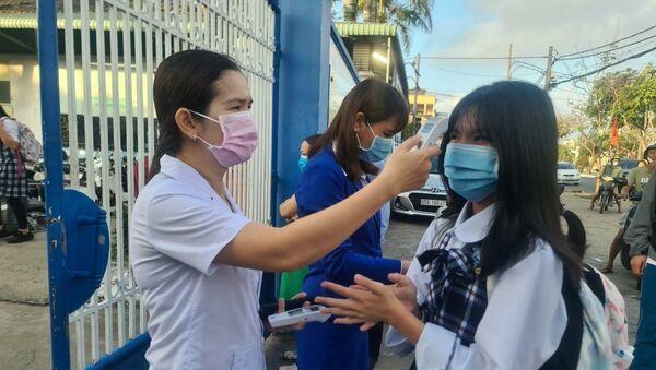 Đo thân nhiệt trước khi vào lớp tại trường liên cấp THCS - THPT Thái Bình Dương. - Sputnik Việt Nam