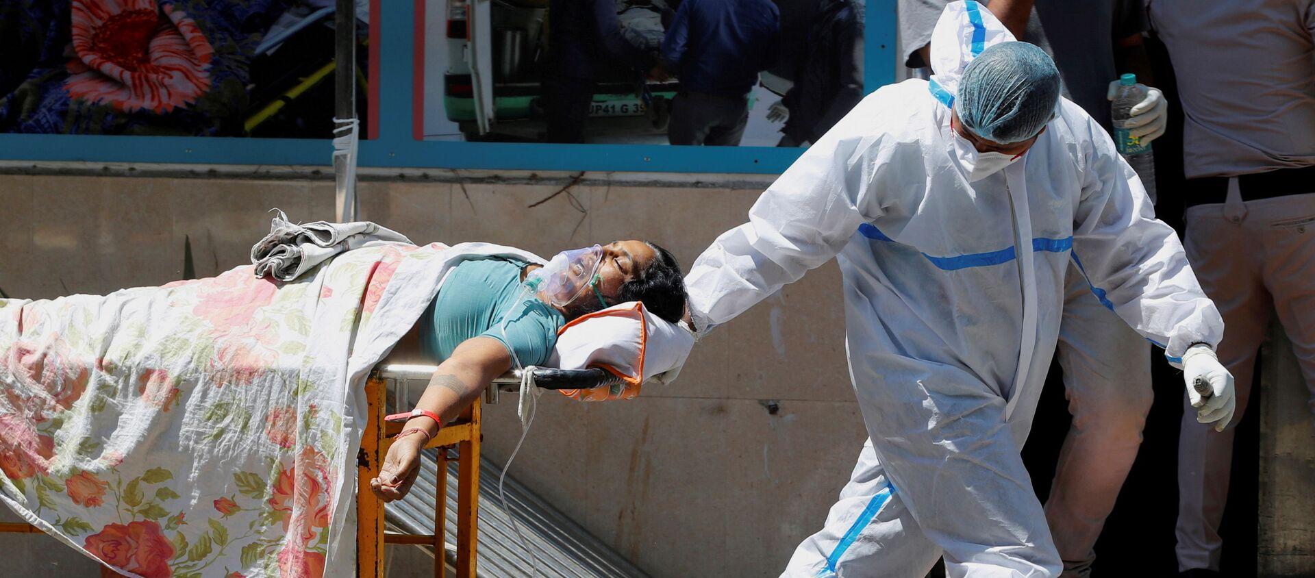 FILE PHOTO: Một nhân viên y tế mang thiết bị bảo vệ cá nhân (PPE) bế một bệnh nhân mắc bệnh do coronavirus (COVID-19) bên ngoài khu cấp cứu tại bệnh viện Guru Teg Bahadur, ở New Delhi, Ấn Độ, ngày 24 tháng 4 năm 2021. - Sputnik Việt Nam, 1920, 05.05.2021