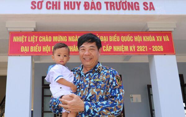 Chuẩn Đô đốc Hải quân nhân dân Việt Nam Phan Tuấn Hùng và bé Lâm Nhật Kiến Huy (18 tháng tuổi, công dân trị trấn Trường Sa) trước Sở chỉ huy đảo Trường Sa.  - Sputnik Việt Nam