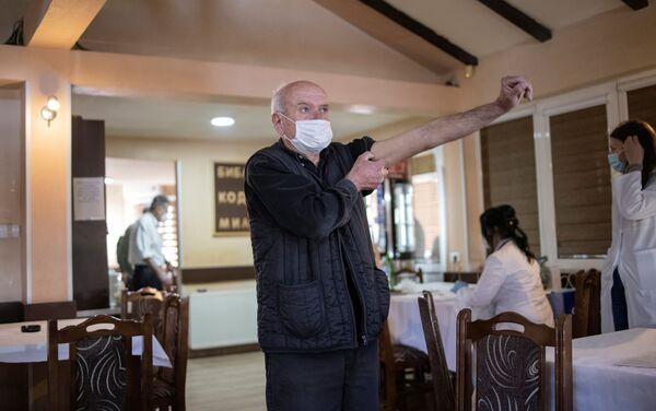 Một người đàn ông được tiêm vắc xin chống lại coronavirus trong nhà hàng Kragujevac, Serbia. - Sputnik Việt Nam