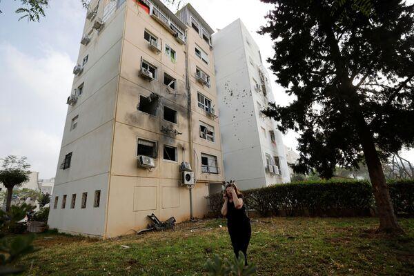 Người phụ nữ cạnh tòa nhà dân bị hư hại ở Ashkelon do tên lửa phóng từ Dải Gaza  - Sputnik Việt Nam