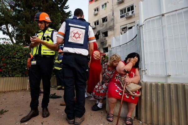 Các nhân viên y tế Israel đứng cạnh những người phụ nữ gần ngôi nhà bị hư hại ở Ashkelon do tên lửa phóng từ Dải Gaza  - Sputnik Việt Nam