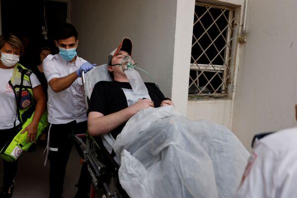 Các nhân viên y tế Israel sơ tán người đàn ông bị thương do tên lửa phóng từ Dải Gaza rơi trúng tòa nhà dân ở Ashkelon, miền nam Israel - Sputnik Việt Nam