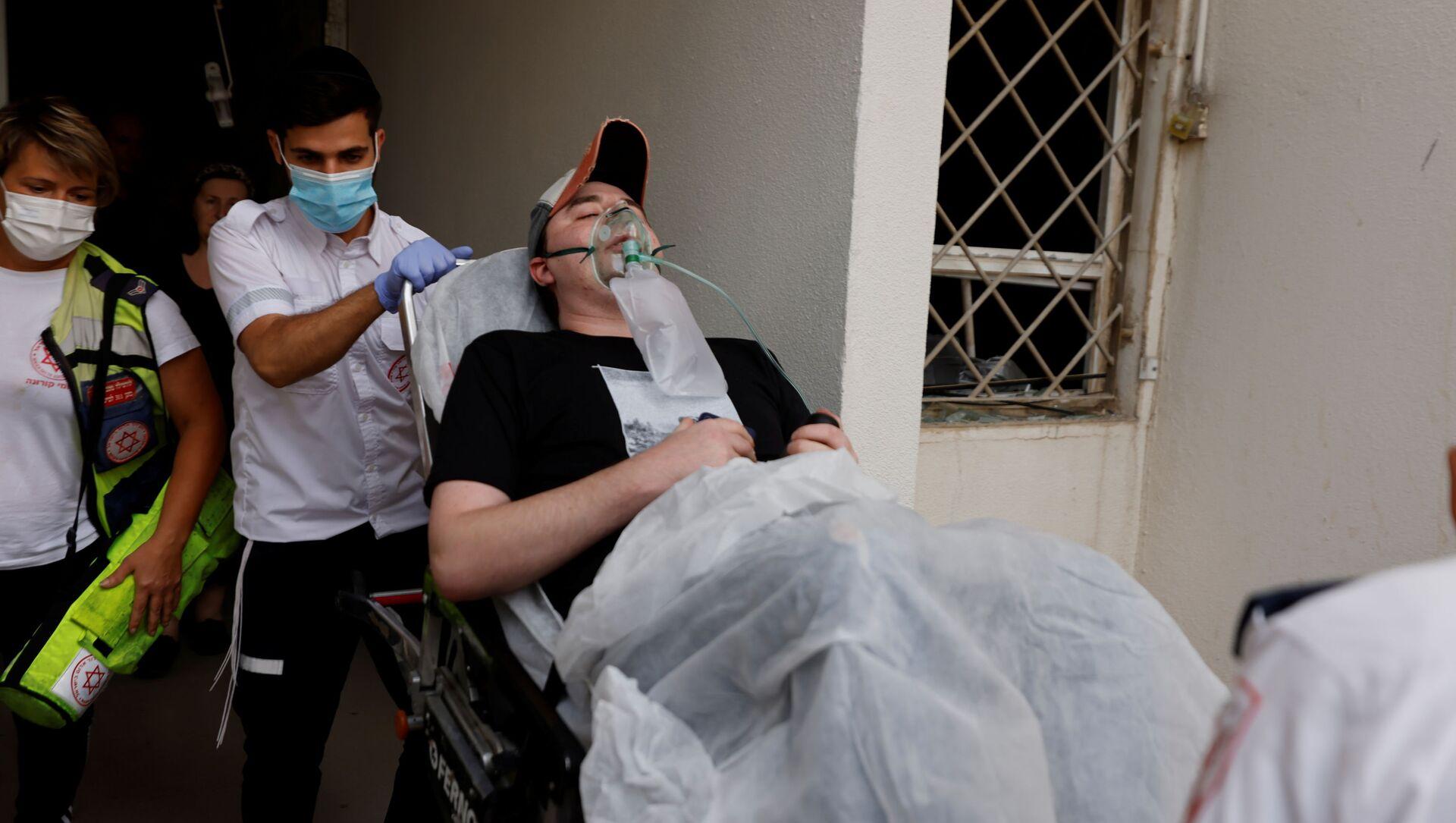 Các nhân viên y tế Israel sơ tán người đàn ông bị thương do tên lửa phóng từ Dải Gaza rơi trúng tòa nhà dân ở Ashkelon, miền nam Israel - Sputnik Việt Nam, 1920, 11.05.2021