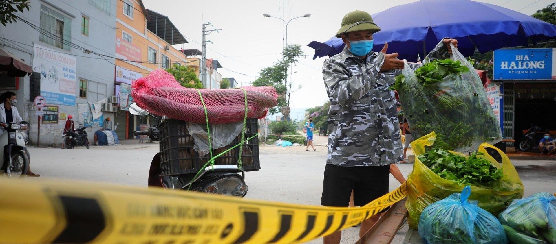 Người dân cung cấp nhu yếu phẩm vào khu cách ly theo đúng quy trình dịch tế tại chốt kiểm soát dịch tổ dân phố My Điền 1. - Sputnik Việt Nam, 1920, 11.05.2021