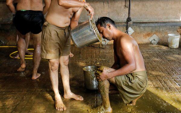 Công nhân Ấn Độ Uddhav Bhatia bôi phân bò lên cơ thể để tăng cường khả năng miễn dịch và sức đề kháng chống coronavirus. - Sputnik Việt Nam