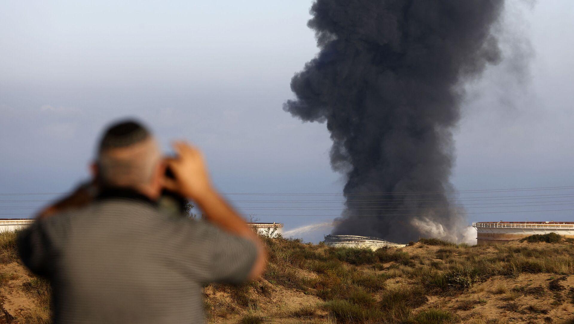 Một người đàn ông Israel nhìn từ xa khi khói bốc lên vào sáng sớm ngày 12 tháng 5 năm 2021 từ nhà máy lọc dầu của Ashkelon, bị trúng tên lửa Hamas vào ngày hôm trước, ở thành phố phía nam Israel, gần Dải Gaza - Sputnik Việt Nam, 1920, 17.05.2021