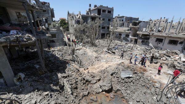 Người Palestine tập trung gần những ngôi nhà bị phá hủy sau cuộc không kích và pháo kích của Israel ở Dải Gaza - Sputnik Việt Nam