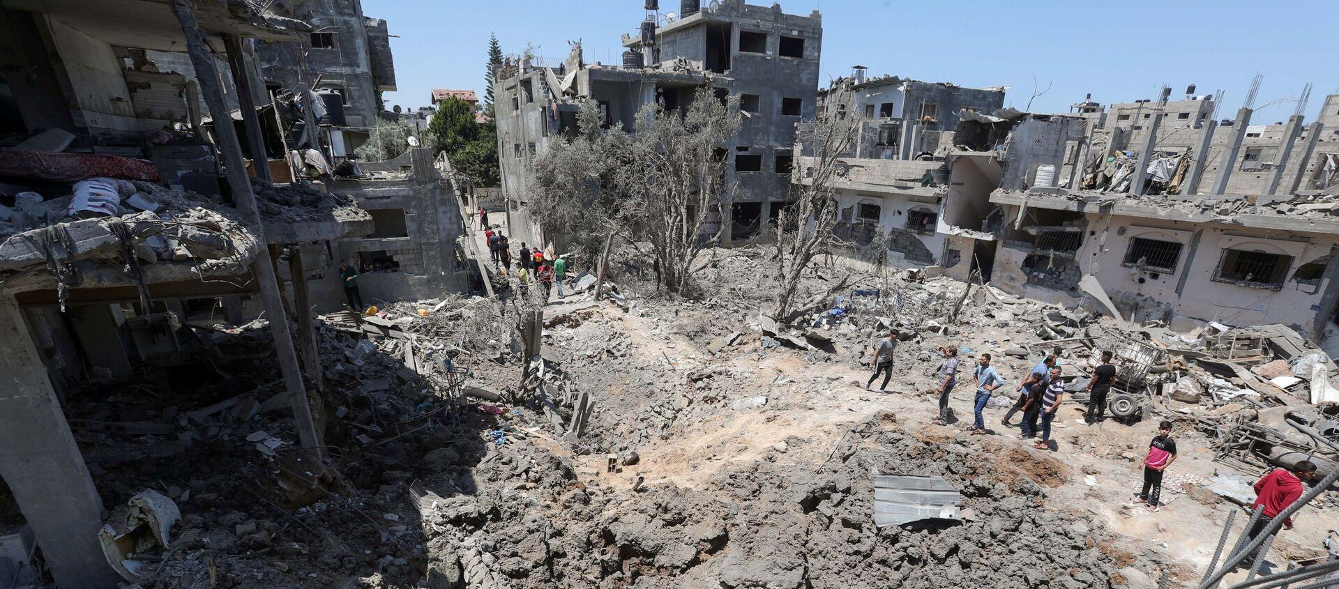 Người Palestine tập trung gần những ngôi nhà bị phá hủy sau cuộc không kích và pháo kích của Israel ở Dải Gaza - Sputnik Việt Nam, 1920, 14.05.2021