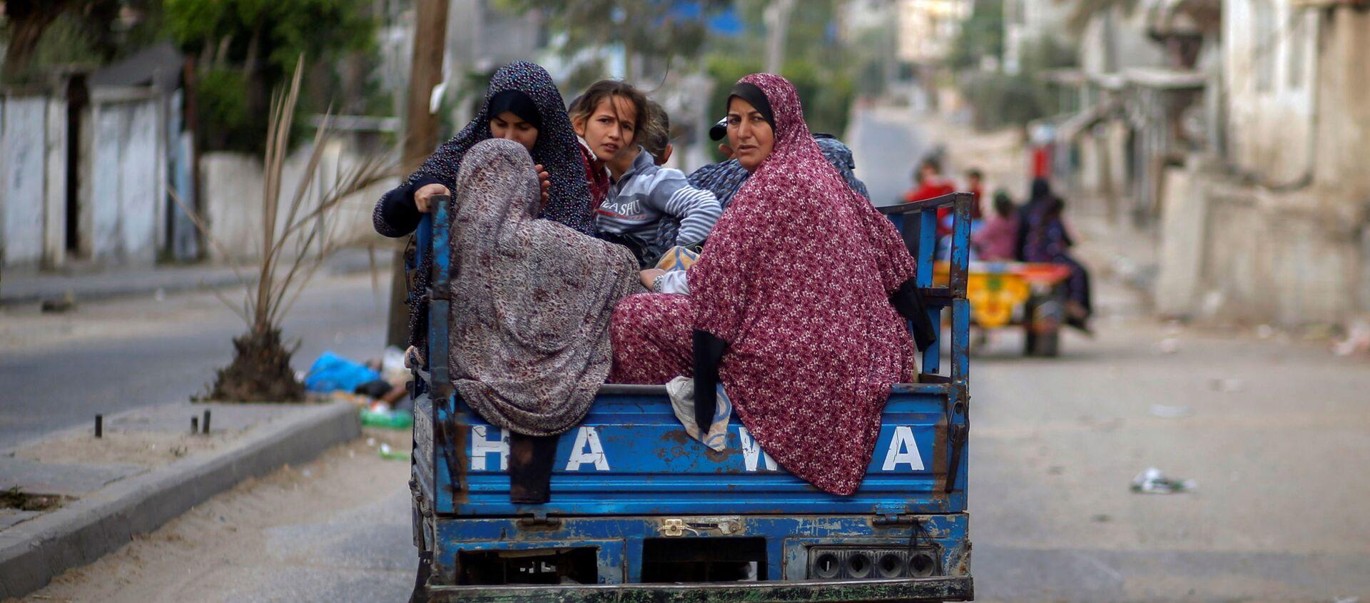 Người Palestine trên xe kéo ô tô chạy khỏi nhà của họ trong các cuộc không kích và pháo binh của Israel - Sputnik Việt Nam, 1920, 16.05.2021