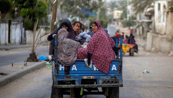 Người Palestine trên xe kéo ô tô chạy khỏi nhà của họ trong các cuộc không kích và pháo binh của Israel - Sputnik Việt Nam