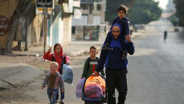 Người Palestine chạy trốn khỏi nhà của họ trong cuộc không kích của Israel và pháo binh ở Dải Gaza - Sputnik Việt Nam