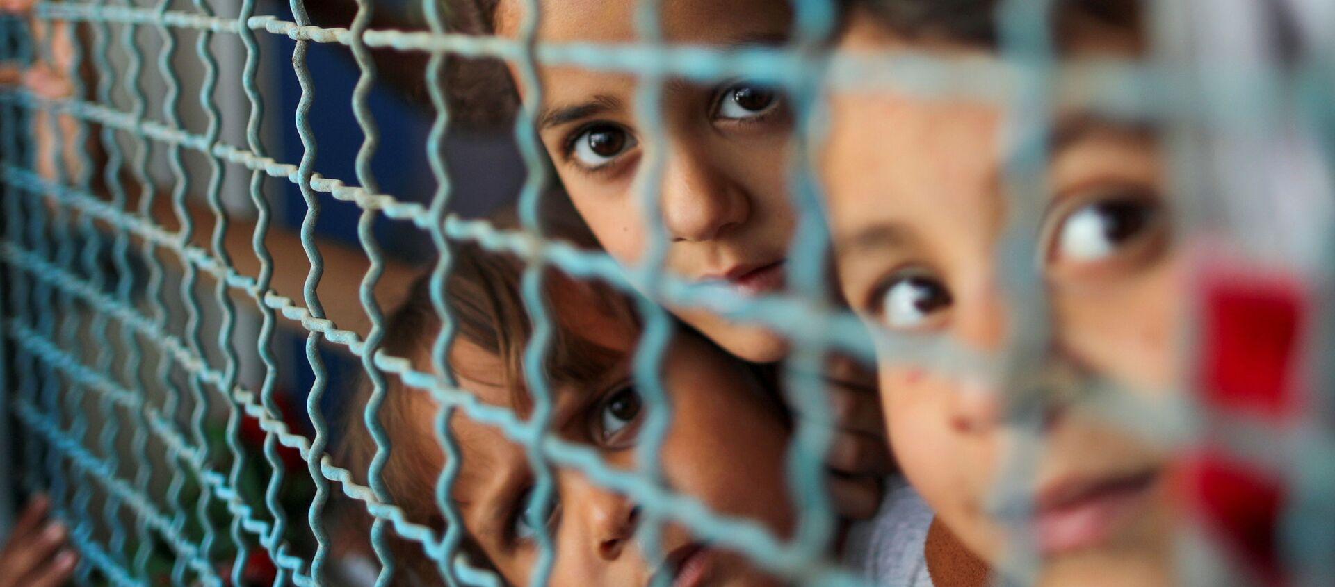 Trẻ em Palestine phải ra khỏi nhà bởi các cuộc không kích và pháo binh của Israel đang nhìn qua lan can cửa sổ của trường học do Liên hợp quốc điều hành, nơi họ trú ẩn ở thành phố Gaza - Sputnik Việt Nam, 1920, 04.06.2021