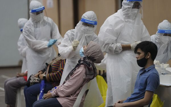 Nhân viên y tế thu thập mẫu từ người dân trong quá trình xét nghiệm coronavirus tại trung tâm xét nghiệm COVID-19 ở Ulu Klang, ngoại ô Kuala Lumpur, Malaysia. - Sputnik Việt Nam
