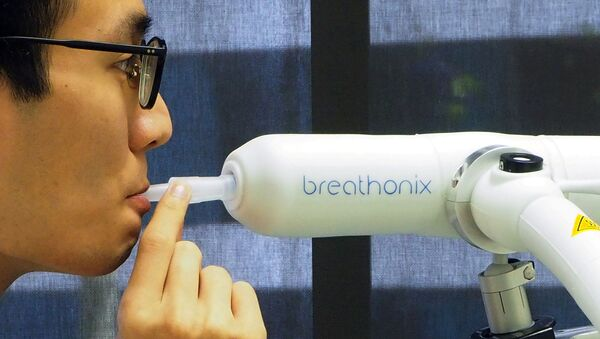 Nhân viên giới thiệu mẫu xét nghiệm phát hiện COVID-19 qua hơi thở do công ty Breathonix có trụ sở tại Singapore phát triển. - Sputnik Việt Nam