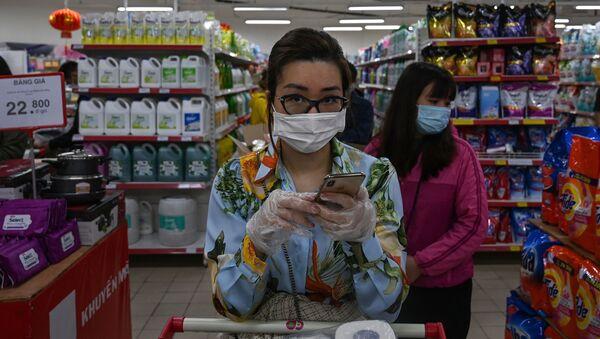 Cô gái đeo khẩu trang và găng tay đứng xếp hàng trong siêu thị Hà Nội. - Sputnik Việt Nam