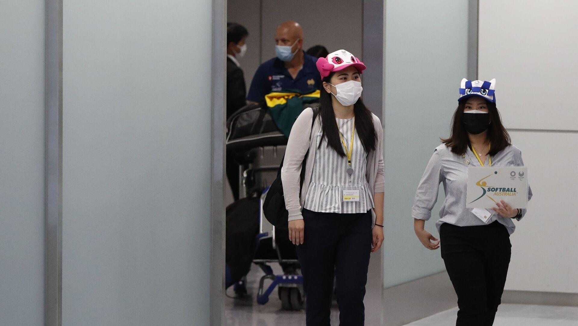 Các cô gái đội mũ in hình linh vật chính thức của Thế vận hội Olympic và Paralympic Tokyo tại sân bay Narita. - Sputnik Việt Nam, 1920, 02.06.2021