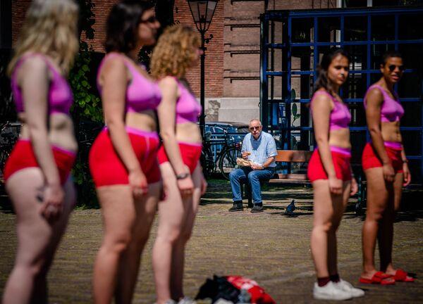 Người đàn ông nhìn các nữ sinh biểu tình ở Plaine, trung tâm thành phố cổ The Hague - Sputnik Việt Nam