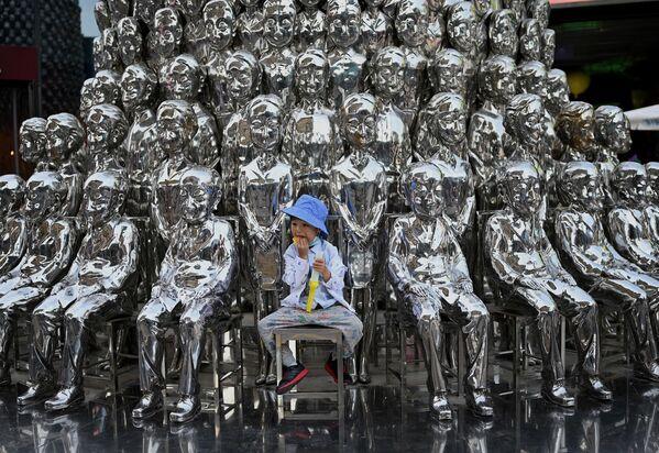 Cậu bé ngồi trên ghế giữa các tác phẩm điêu khắc được trưng bày tại một trung tâm thương mại vào Ngày Quốc tế Thiếu nhi ở Bắc Kinh - Sputnik Việt Nam