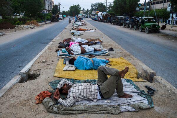 Công nhân ngủ trên dải phân cách một con phố ở thành phố cảng Karachi, Pakistan - Sputnik Việt Nam