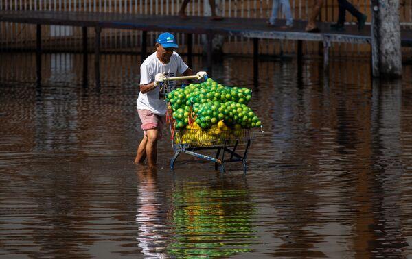 Một người đàn ông đẩy xe trái cây đi xuống con đường ngập lụt ở trung tâm thành phố Manaus, Brazil - Sputnik Việt Nam