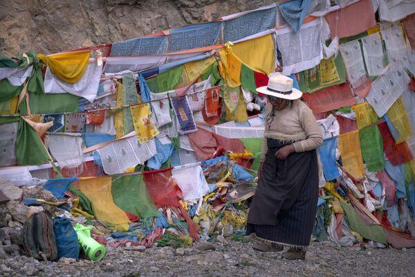Người phụ nữ đi ngang qua những lá cờ cầu nguyện tại một ngôi chùa Phật giáo ở Namtso, Tây Tạng - Sputnik Việt Nam