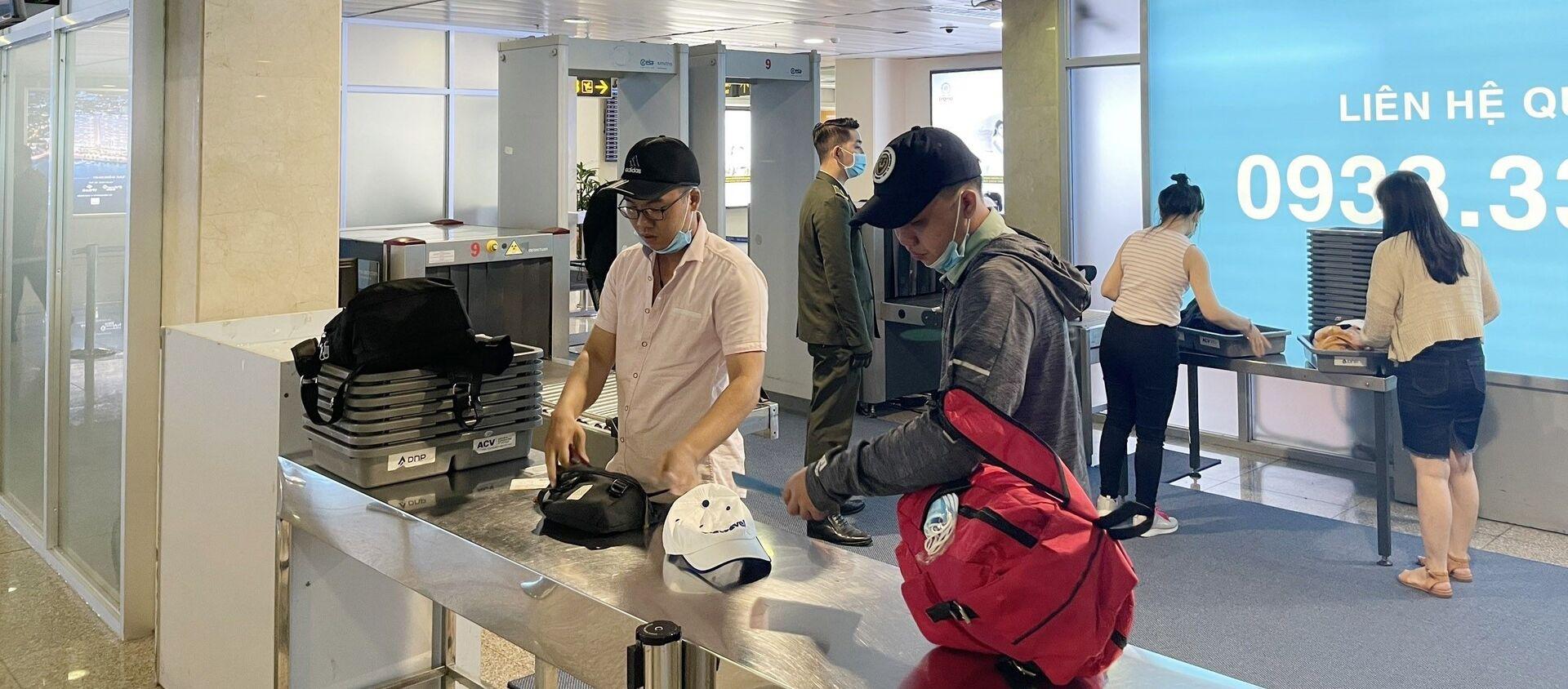 Hành khách thực hiện thủ tục soi chiếu an ninh tại các máy mới được lắp đặt bổ sung. - Sputnik Việt Nam, 1920, 05.06.2021
