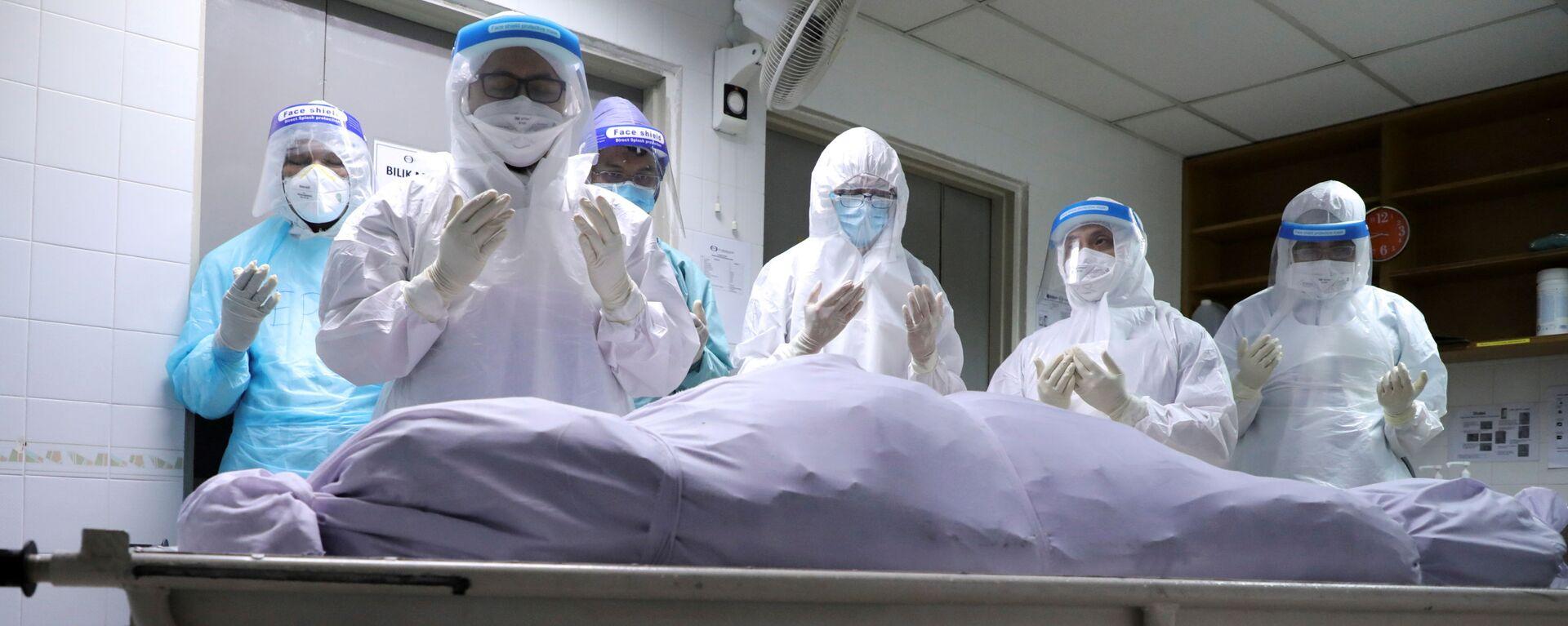 Người nhà của một nạn nhân chết vì COVID đang cầu nguyện tại nhà xác bệnh viện ở Kuala Lumpur, Malaysia. - Sputnik Việt Nam, 1920, 09.06.2021