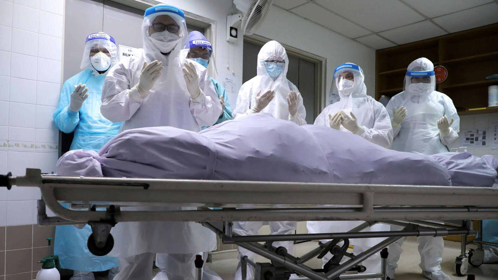 Người nhà của một nạn nhân chết vì COVID đang cầu nguyện tại nhà xác bệnh viện ở Kuala Lumpur, Malaysia. - Sputnik Việt Nam, 1920, 27.09.2021