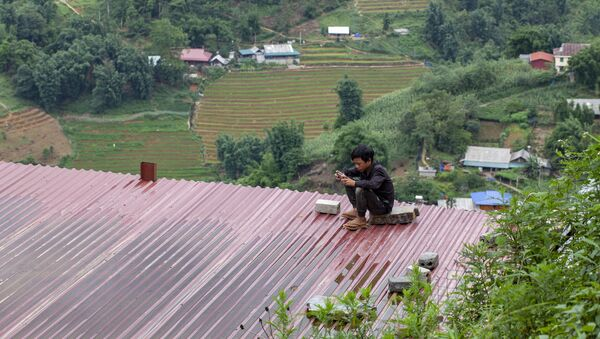 Cậu bé ngồi trên nóc tòa nhà với chiếc điện thoại thông minh, Việt Nam - Sputnik Việt Nam