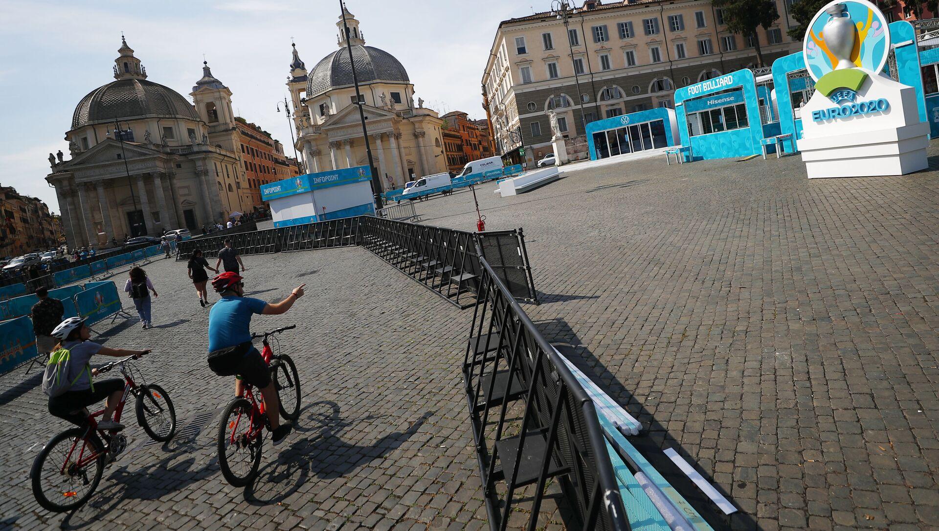 Những người đi xe đạp trong khu vực dành cho người hâm mộ ở Piazza del Popolo ở Rome, khu vực đang được trang trí chuẩn bị  cho UEFA EURO 2020. - Sputnik Việt Nam, 1920, 10.06.2021