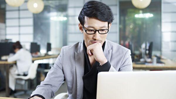 Người đàn ông đang ngồi bên máy laptop trong văn phòng. - Sputnik Việt Nam