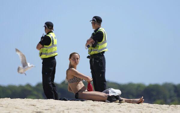 Người phụ nữ trên bãi biển ở Cornwall với cảnh sát phía sau - Sputnik Việt Nam