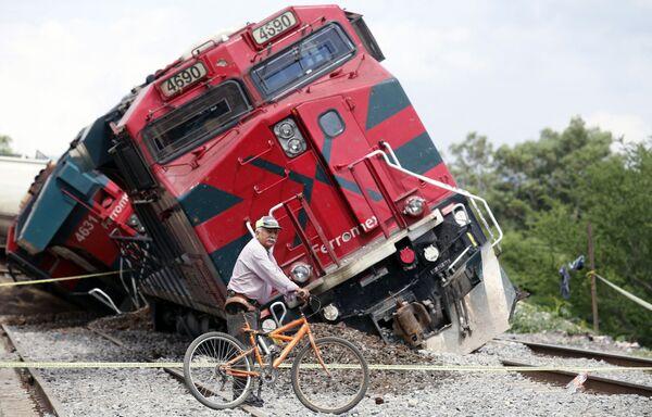 Người đàn ông đi xe đạp qua đoàn tàu trật bánh ở khu phố San Isidro Mazatepec, Tala, bang Jalisco, Mexico - Sputnik Việt Nam