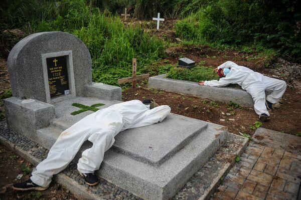 Công nhân mặc đồ bảo hộ nghỉ ngơi sau khi chôn cất nạn nhân nhiễm coronavirus (COVID-19) ở Bandung, Indonesia - Sputnik Việt Nam