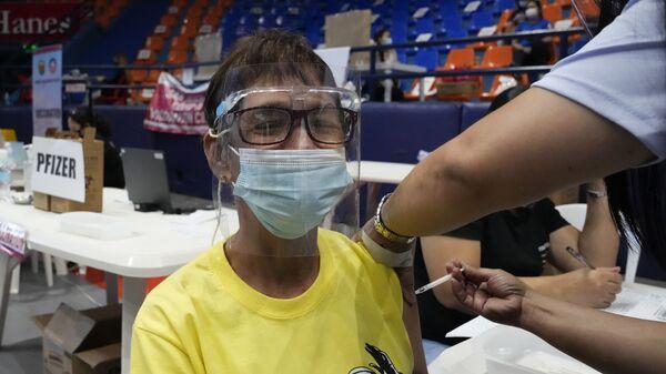 Một phụ nữ đang được tiêm vaccine Pfizer chống coronavirus ở Philippines. - Sputnik Việt Nam
